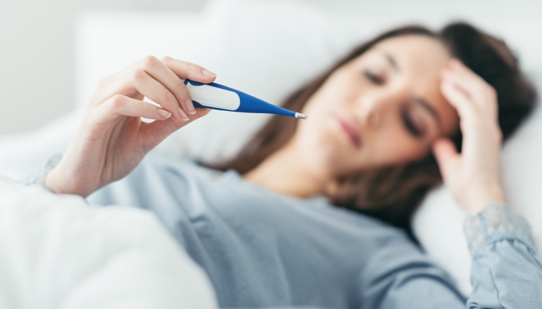 Sieviete ar saaukstēšanos guļ gultā un skatās uz termometru