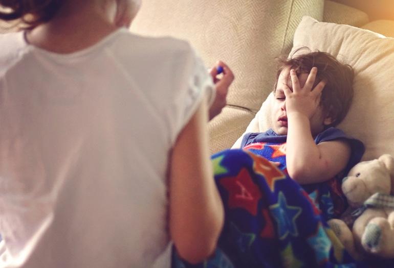 Slims bērns ar mitru klepu guļ segā un ar roku tur savu galvu