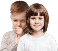 Maza meitene smaida un stāv priekšā mazam zēnam, kuram ir mitrs klepus
