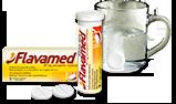 Шипучая таблетка растворяется в воде рядом с упаковкой с Flavamed® 60 мг шипучими таблетками для лечения влажного кашля